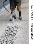 worker of road construction drilling cement ground - stock photo