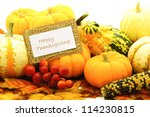 Happy Thanksgiving card among a group of pumpkins and gourds - stock photo