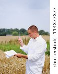 Agriculture scientist or student in the field verifying results of experiment - stock photo