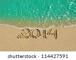 2014 inscription on the sand near the azure sea. - stock photo