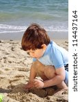 Young boy playing in the sand on the beach - stock photo