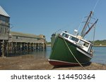Old abandoned fish and shrimp processing wharfs and buildings at low tide on the banks of the Penobscot narrows separating Canada and the United states - stock photo