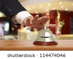 Hand of a businessman using a hotel bell - stock photo