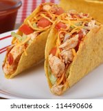 Two chicken tacos with tomato and cheese - stock photo