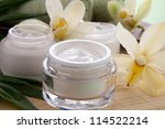 White Cymbidium orchid flower and jar of moisturizing face cream for spa treatment. - stock photo