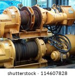 Large industrial winches are used to haul in steel cables - stock photo