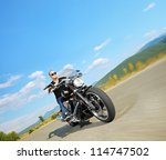 Biker riding a customized motorcycle on an open road - stock photo