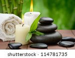 zen basalt stones and candle on the wooden mat - stock photo
