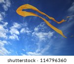 Yellow kite soaring in blue sky - stock photo