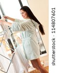 Beautiful woman hanging freshly washed clothes on the rack - stock photo