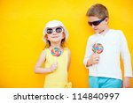 Adorable little kids with colorful lollipops - stock photo