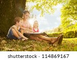Mother reading a book with her son and daughter - stock photo