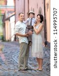 Young family of three in city street - stock photo