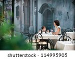 Mother and son sitting in cafe - stock photo