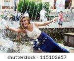 Beautiful girl relaxing with a fountain .
