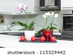 Purple and white orchids in modern kitchen - stock photo
