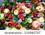 Fall arrangement with fruits and flowers - stock photo