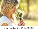 Young Woman Smelling Flowers I...