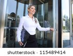 A pretty blonde business woman leaving the office building through glass doors - stock photo
