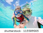 Underwater portrait of father and son snorkeling together - stock photo