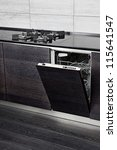 Open dish washer machine and gas-stove on black hardwood kitchen - stock photo