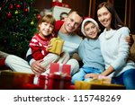 Portrait of friendly family looking at camera on Christmas evening - stock photo
