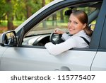alluring young woman driving the car and smiling - stock photo