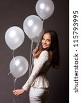 Beautiful fashion woman in studio with white balloons - stock photo