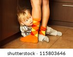 Boy hiding behind mothers legs - stock photo