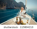 beautiful young girl eating and talking on a mobile phone on a boat sailing along the rocky shore of the sea - stock photo