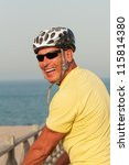 Portrait of a happy smiling active older man with a cycling helmet on a summer evening - stock photo