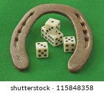 An horseshoe over green background with five dice - stock photo