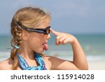 Girl with sunglasses at the beach sticking out  tongue - stock photo