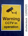 A Cctv Warning Sign On A Blue...