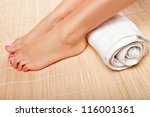 Womans feet with a rolled towel behind the ankles as she waits for a beautician to complete a beauty treatment at a spa - stock photo