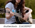 Teenage girl playing an acoustic guitar - stock photo