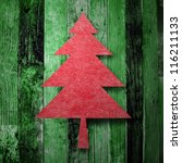 Red Christmas tree on green wooden texture - stock photo