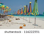 Folded sunshades on tropical island beach - stock photo