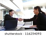 An ethnic man and woman business team handshake at office building - stock photo