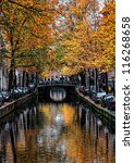 Image of a canal in Amsterdam with beautiful fall trees water reflections. - stock photo