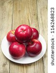 Apples in a plate on a wooden background - stock photo