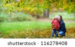 Mother and her little daughter at beautiful autumn park - stock photo