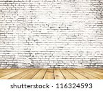 Old brick wall on wood floor - stock photo