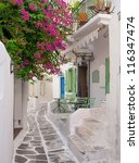 The narrow streets of the Greek islands with bougainvillea flowers. Mykonos. - stock photo