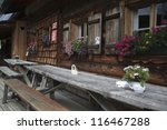 Old wooden Alpine Cabin with outdoor tables and benches in Austria - stock photo