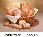 Various breads in basket on canvas tablecloth - stock photo