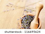 Pestle and mortar with lavender on the oak table with copy-space - stock photo
