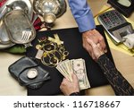 woman receiving cash for gold and silver items - stock photo