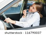 frivolous woman driving the car, painting her lips and talking on the phone - stock photo