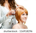Young woman barber makes hairstyle for a girl isolated on white background - stock photo